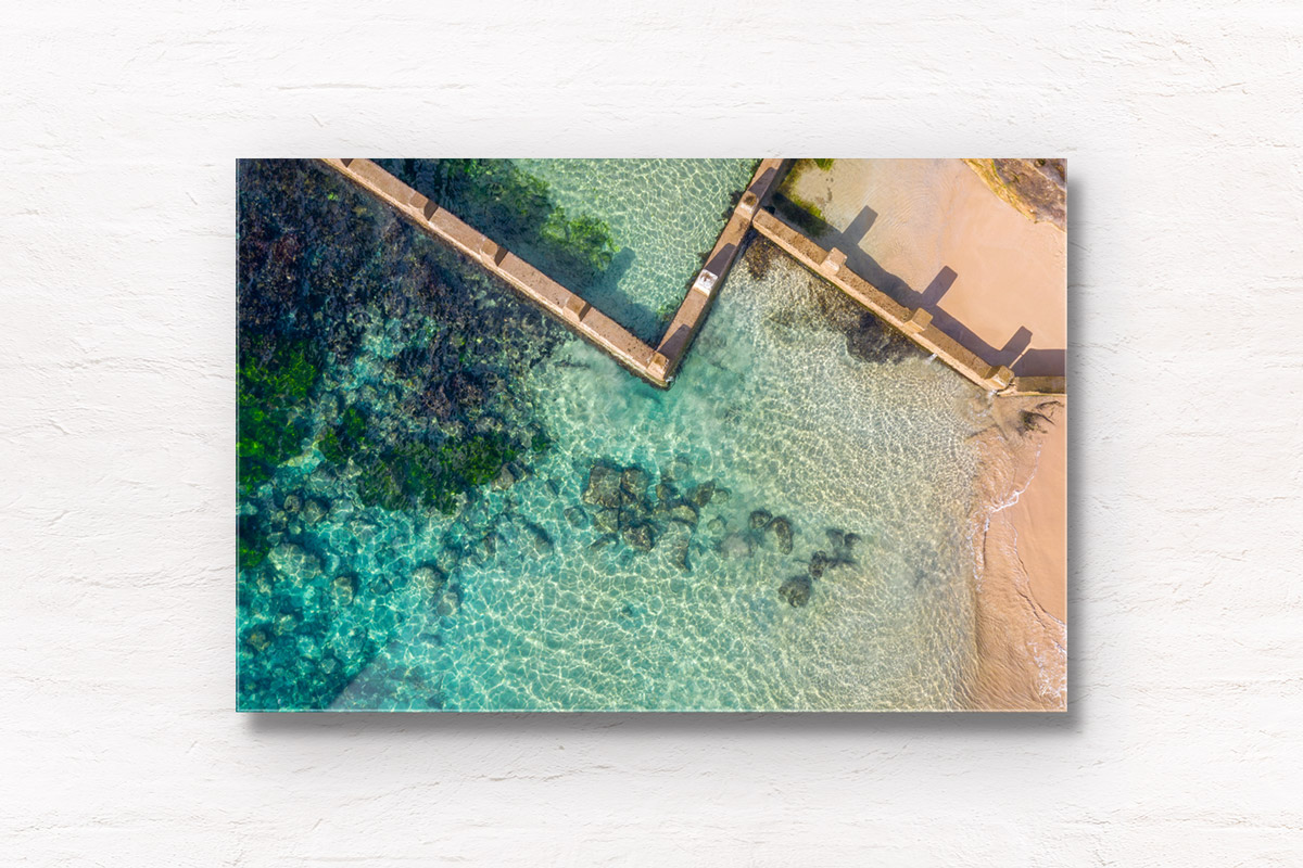 Aerial beach shot above the seaside oceanpool and turquoise waters of Ross Jones Rockpool, Coogee