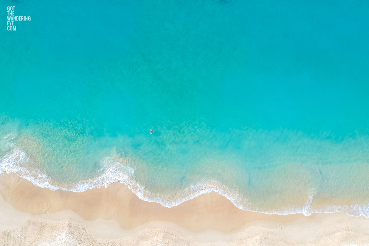 Aerial oceanscape of a lone swimmer enjoying the beautiful calm turquoise waters of Coogee Beach