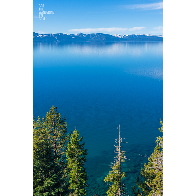 Aerial landscape above the pine trees and turquoise waters of Lake Tahoe, with mountains in the distance