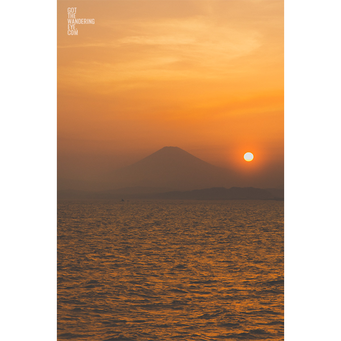 Gorgeous sunset, dropping down into the ocean over the silhouette of Mount Fuji, Japan