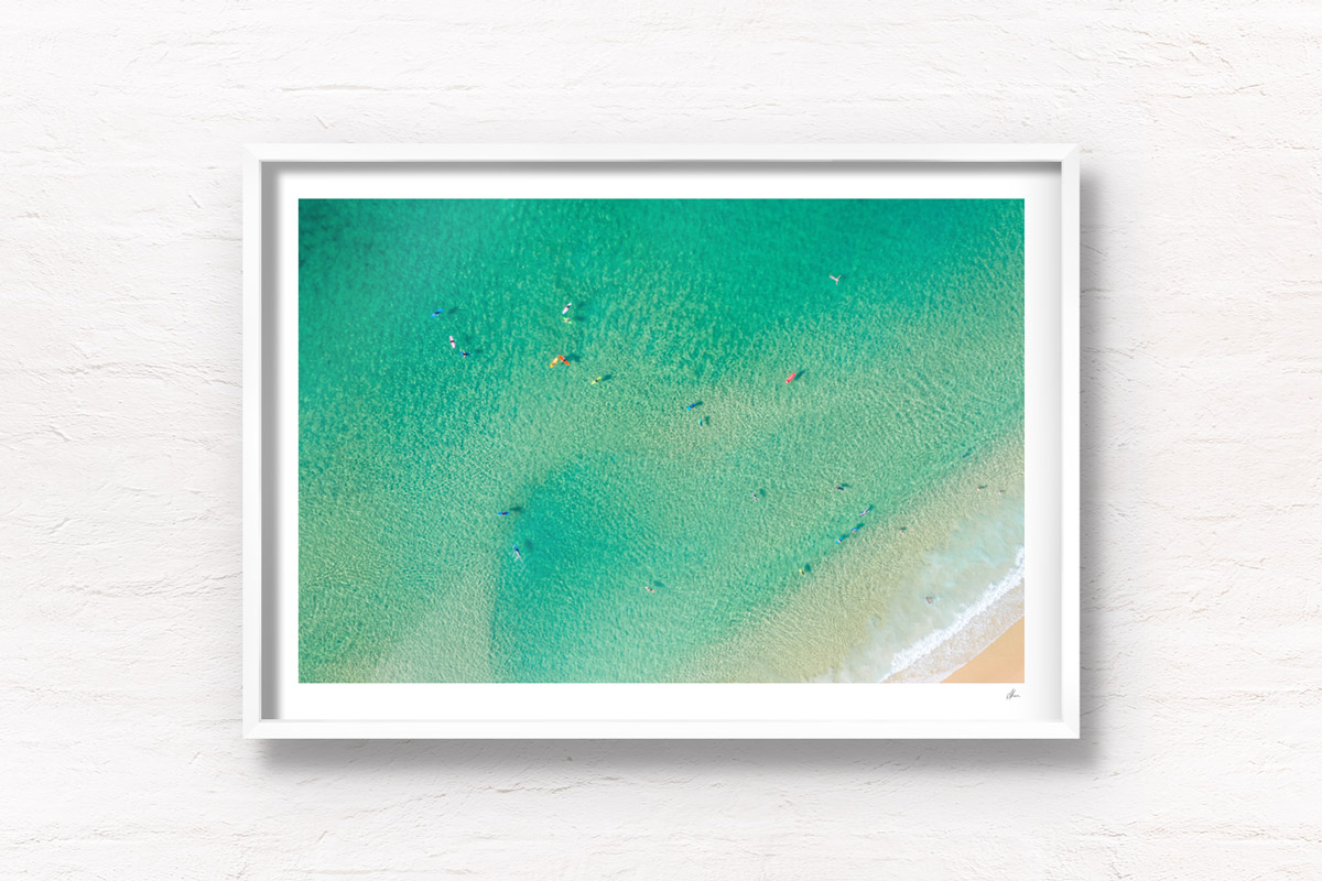 Aerial oceanscape above crystal clear waters on Bondi beach with colourful surfboards