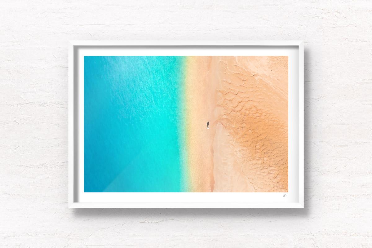 Aerial oceanscape above a woman walkign along deserted south coast beach