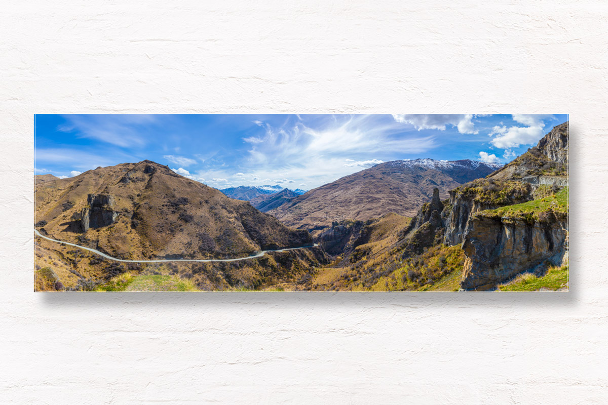 Panoramic of Skippers Canyon's incredible winding roads, dwarfed by mountains, in New Zealand