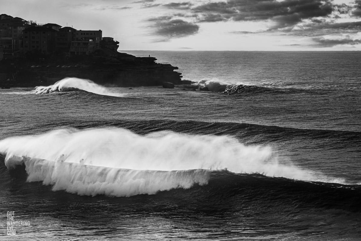 Black and white photo of huge waves crashing over Bondi Beach