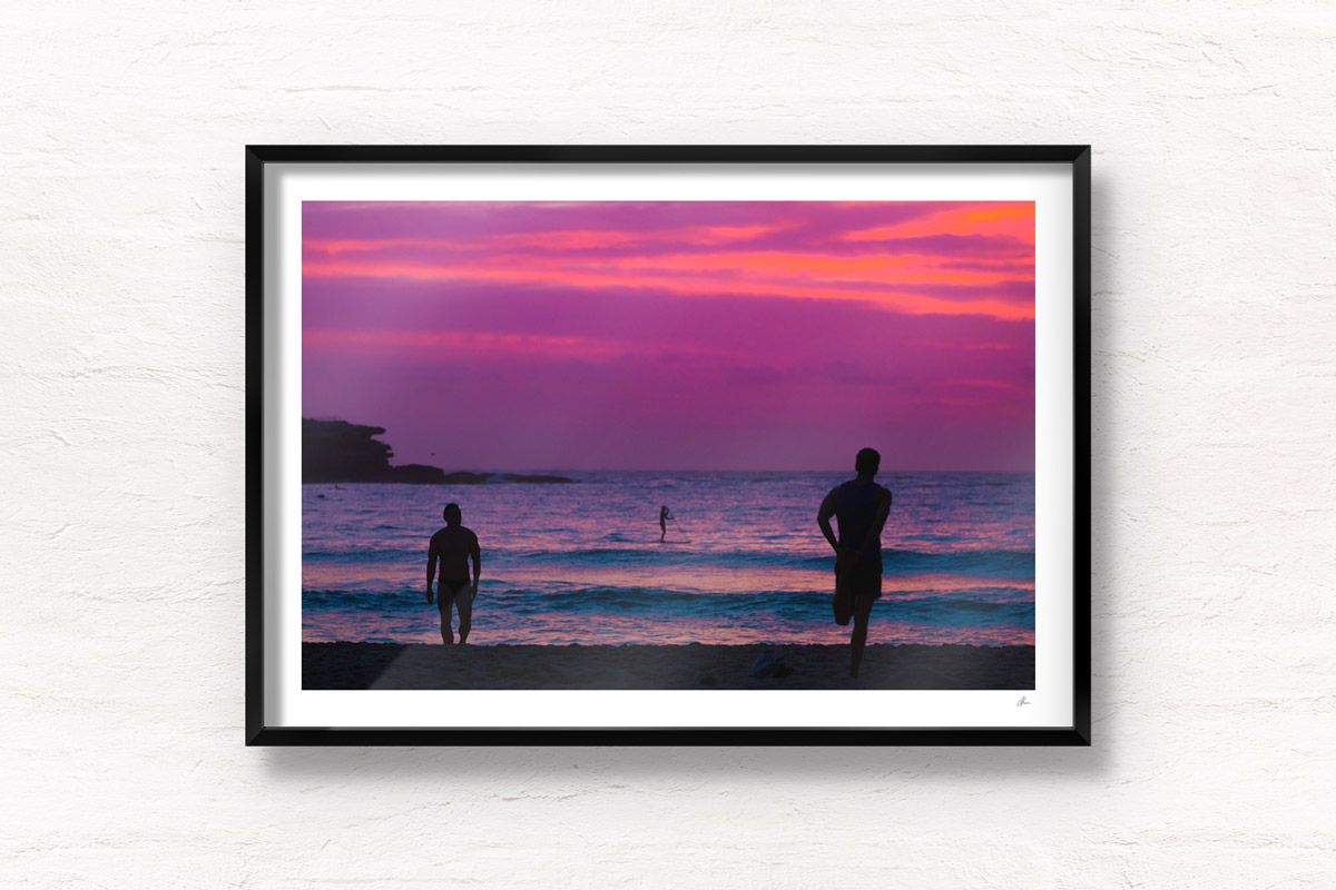 Silhouettes of people enjoy a spectacular pink sky sunrise looking towards Ben Buckler, Bondi Beach