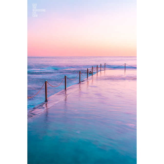 Long exposure of pastel coloured sunrise over Wylie's Baths, ocean pool in Coogee