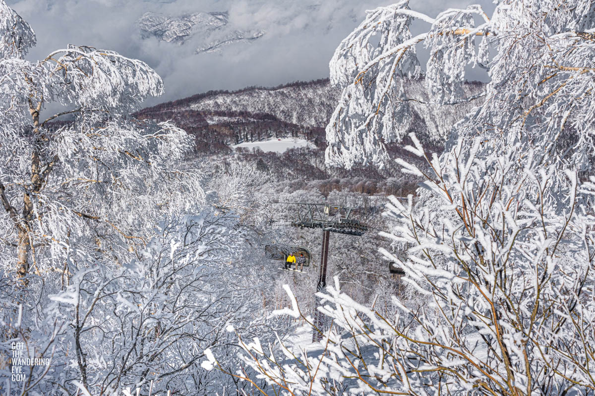 Snowboarders riding chairlift with beautiful snow covered trees over Nozawa Onsen, Japan