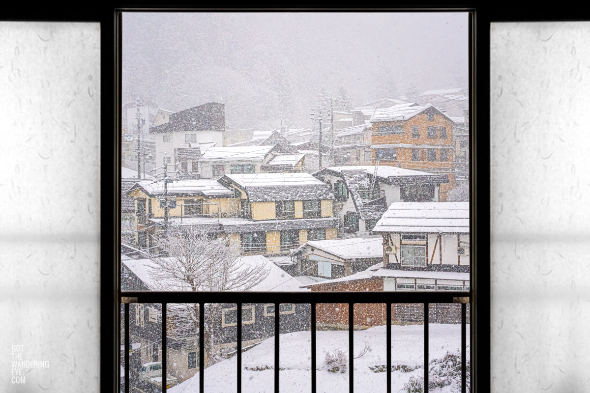 Sliding shoji doors in traditional ryokan opening up to Nozawa Onsen Village, Japan as it snows.