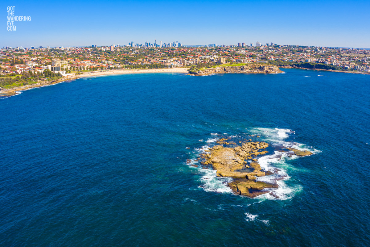 Aerial seascape above Wedding Cake Island looking back to Coogee Beach and the Sydney skyline