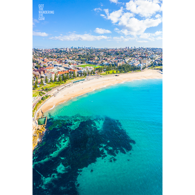 Aerial seascape above turquoise ocean waters of Coogee Beach looking back at the Sydney skyline in the horizon.