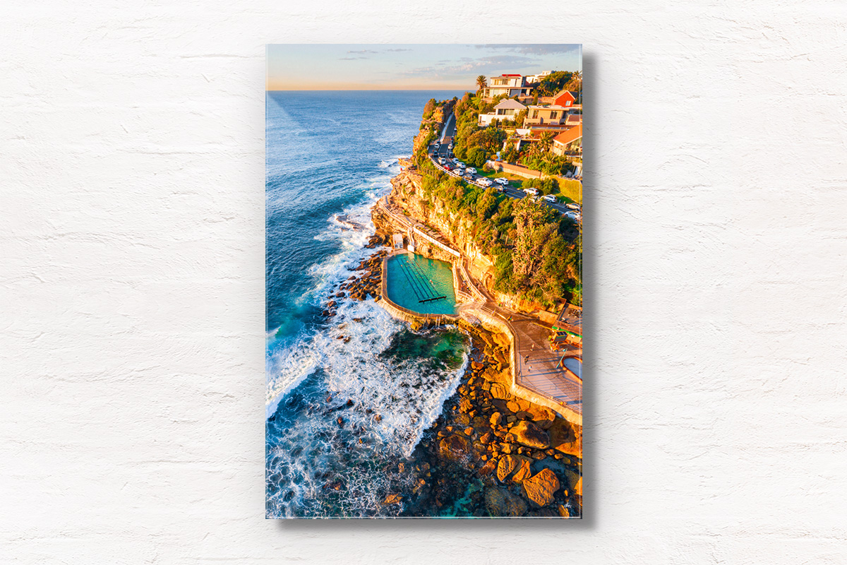 Aerial seascape of Bronte Rockpool bathed in a warm glow from the sunrise during Winter.