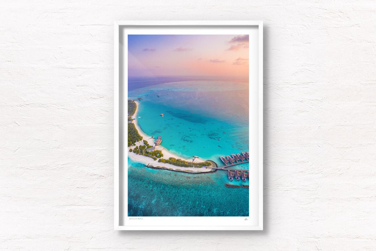 Aerial seascape above a beautiful sunset above the tiny paradise island of Fairmont Maldives.
