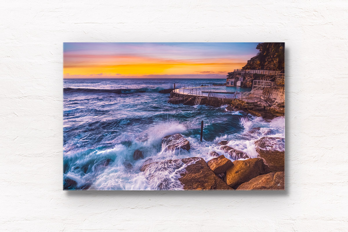 Long exposure of a swimmer stands on the edge of Bronte rockpool watching the sun rise over the horizon.