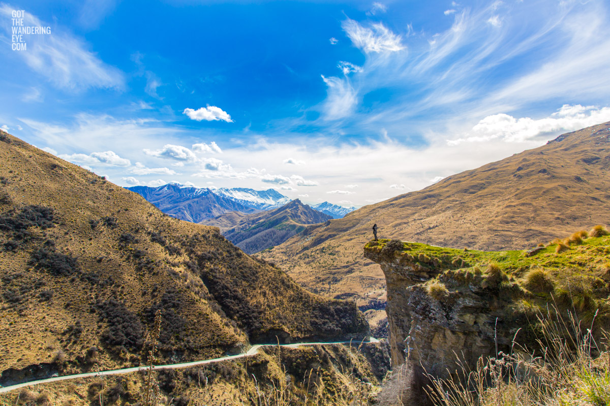 Woman standing on canyons edge admiring the splendid mountainous view of Skippers Canyon in New Zealand