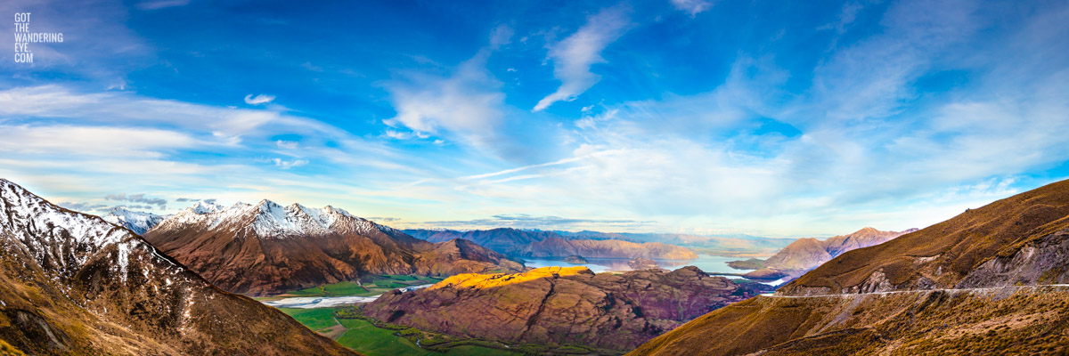The most spectacular panoramic view down from the top of Treble Cone Road over Rocky Mountains to Lake Wanaka, New Zealand