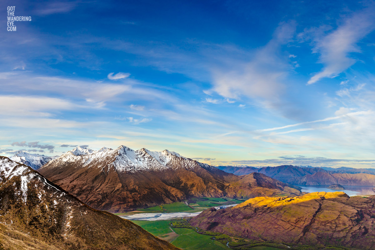 The most spectacular view down from the top of Treble Cone Road over Rocky Mountains to Lake Wanaka, New Zealand