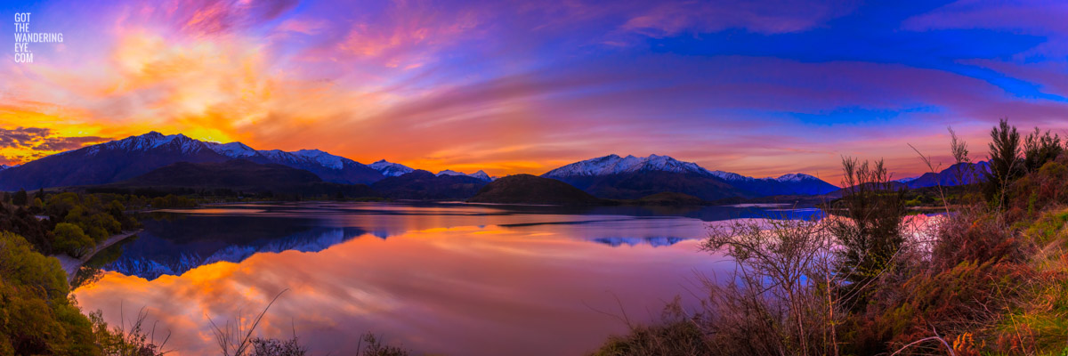 Stunning panoramic silky pink sunset sky with reflection of mountains of Wanaka New Zealand