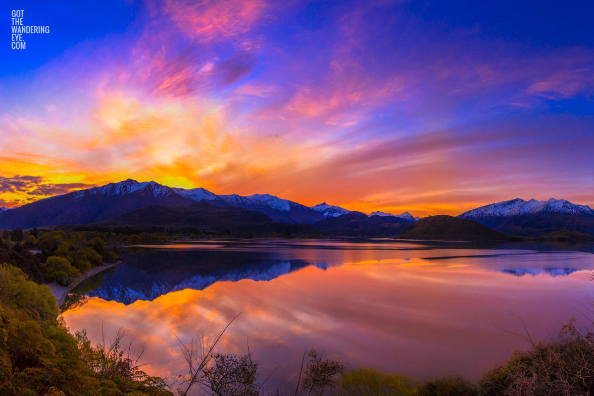 Stunning silky pink sunset sky with reflection of mountains of Wanaka New Zealand