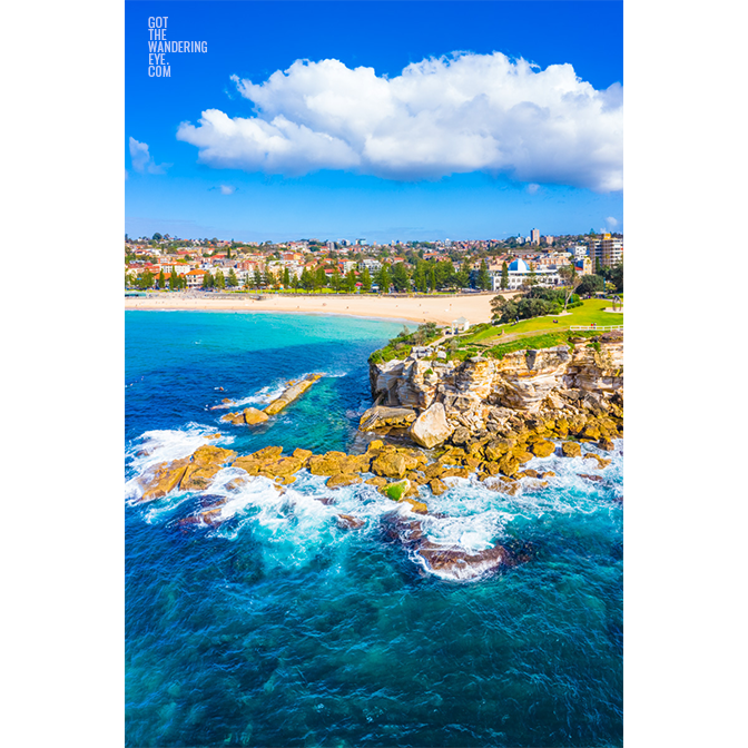 Aerial oceanscape view of Giles Baths, Bogey Hole rockpool, ocean bath from the northern headland of Coogee Beach, with the Coogee Pavilion and Coogee Beach