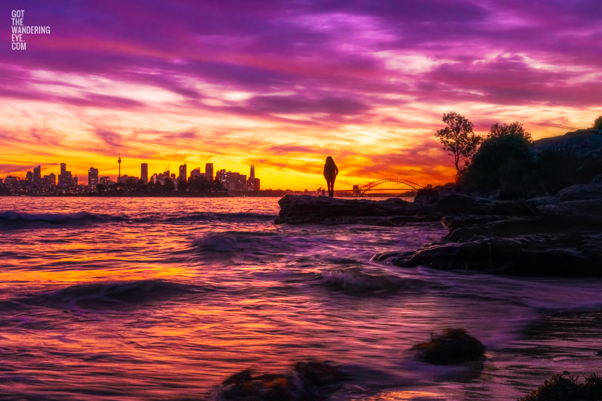 Woman standing admiring a stunning pink sky sunset from Milk Beach looking at the Sydney city skyline