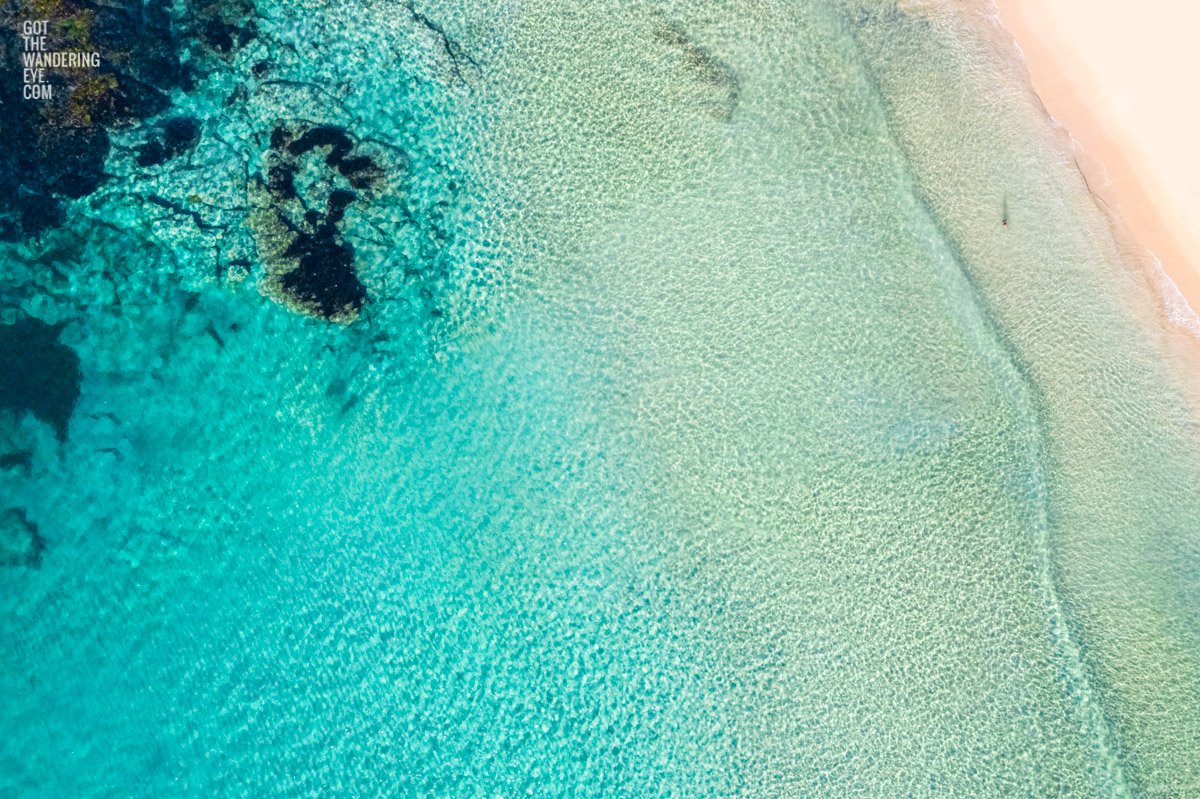 Aerial oceanscape above secluded crystal clear ocean beach waters of South Cronulla Beach