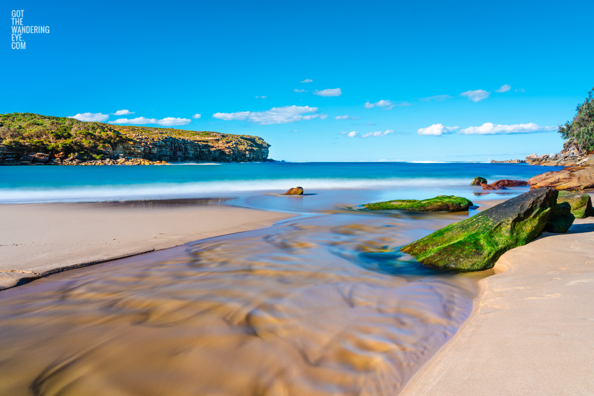 Beautiful long exposure photography of Wattamolla Beach, with waterfall stream flowing into beach, ocean. Royal National Park