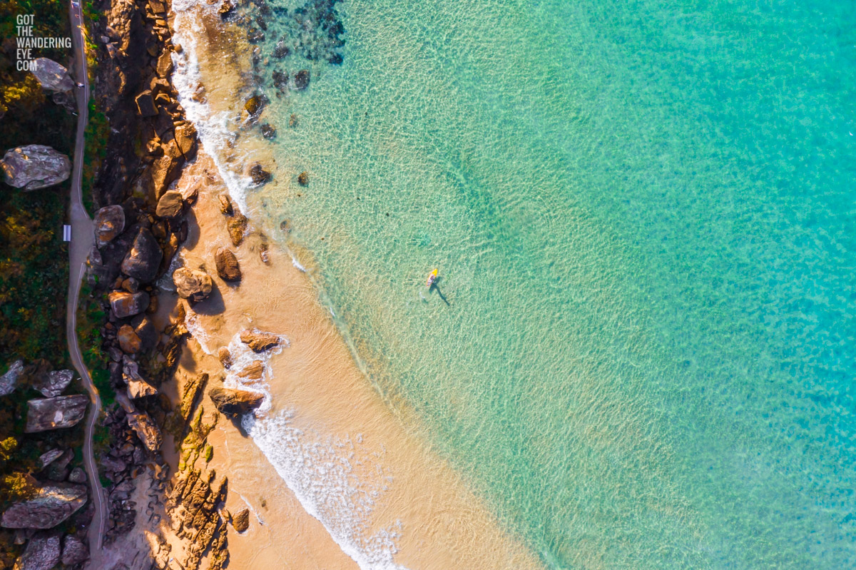 Aerial seascape above Freshwater Beach of a man on paddleboard enjoying the crystal clear ocean.