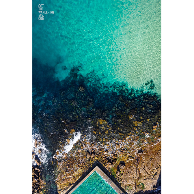 Aerial oceanscape above crystal clear waters of Freshwater Beach. Ocean, rockpool summertime.