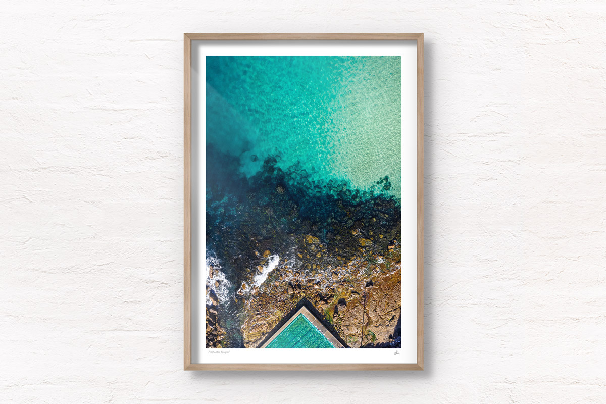 Fine art framed print of a aerial oceanscape above crystal clear waters of Freshwater Beach. Ocean, rockpool summertime.