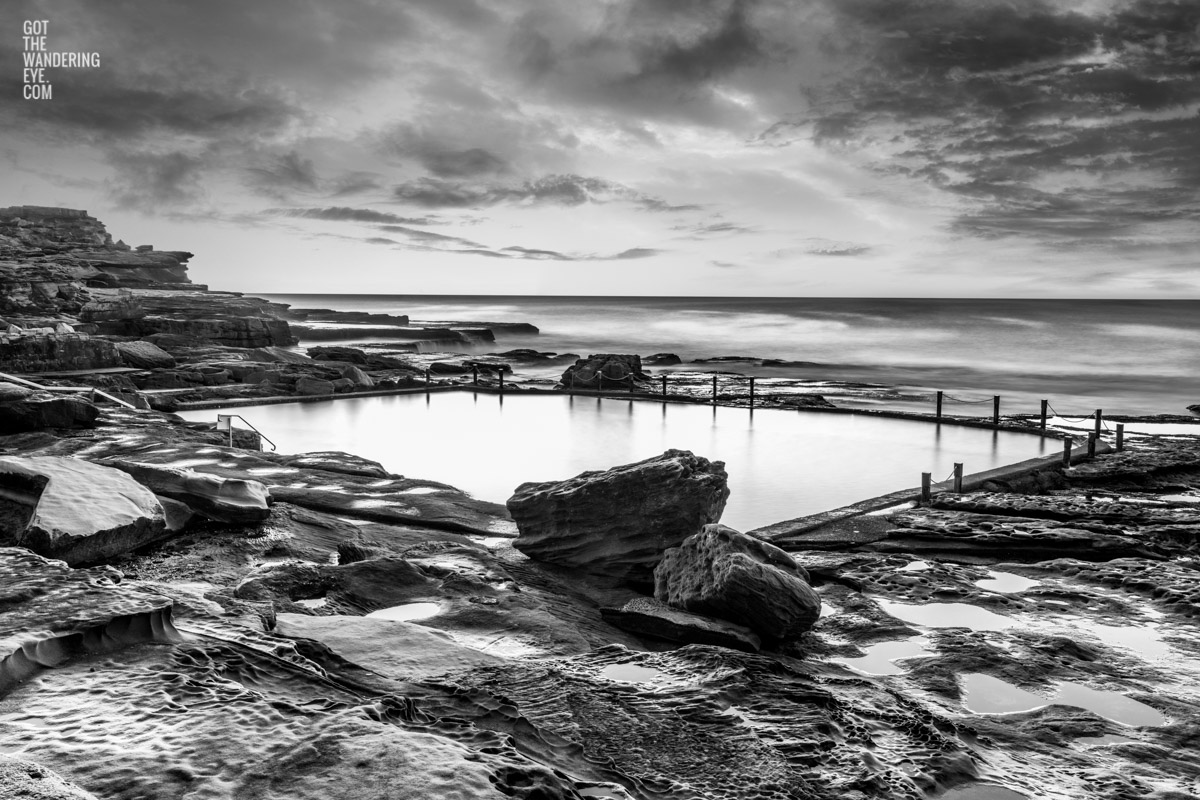 Ocean rockpool in the middle of a rocky beach edge. Mahon Pool, Maroubra on a cloudy moody day