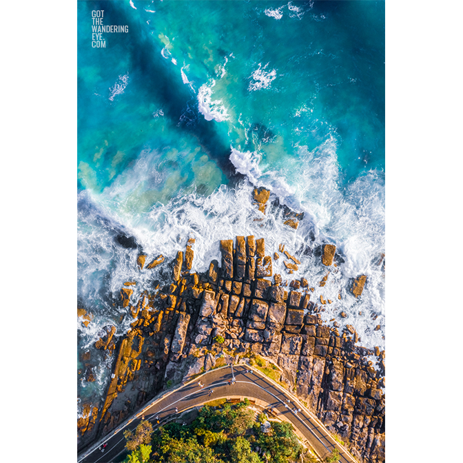 Aerial oceanscape above Marine Parade in Manly. Waves, ocean, beach rocks, walking path