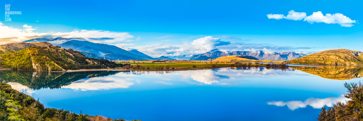Panoramic landscape of Lake Wanaka mountain reflections at Glendu Bay, Wanaka, New Zealand.