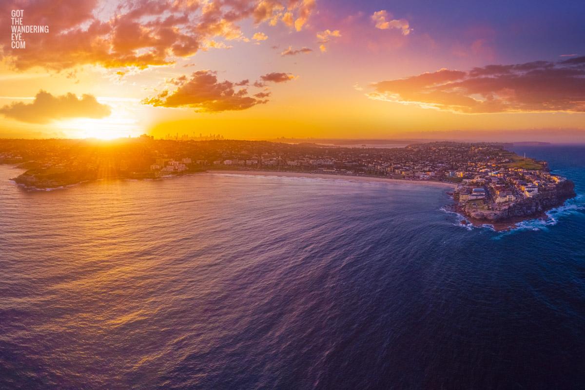Aerial oceanscape above Bondi Beach looking back to a spectacular purple sky sunset setting on the Sydney skyline.