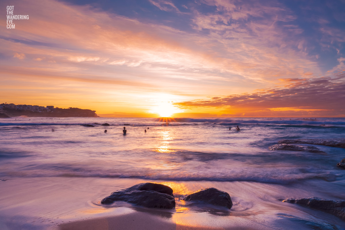 Swimmers enjoying a beautiful sunrise with whispy clouds over Bronte Beach, Sydney by Allan Chan