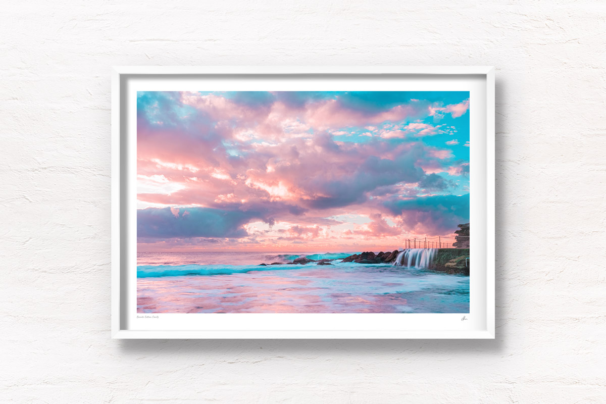 Puffy cotton candy coloured clouds during sunrise at Bronte baths Rockpool.