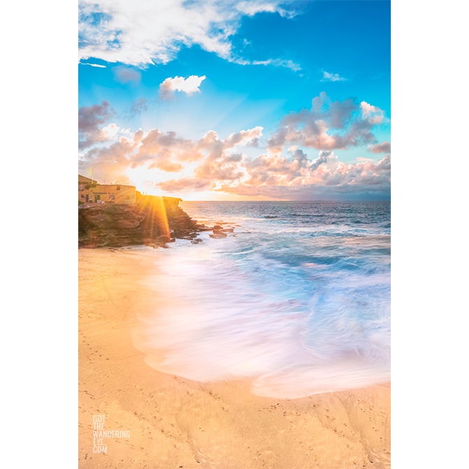 Long exposure of crashing waves flowing onto Tamarama Beach as a sparkling sunrises over Tamarama Surf Life Saving Club.