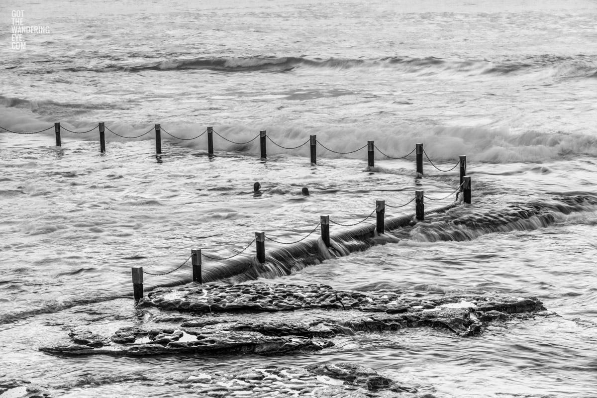 2 woman enjoying a swim at Maroubra. Waves crashing over mahon pool ocean rockpool.