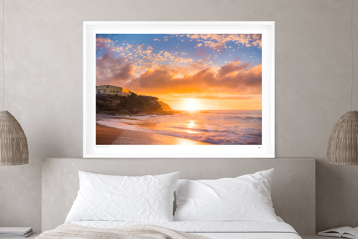A glorious glowing sunrise through puffy clouds rising over Tamarama Beach. Framed print in bedroom decor.
