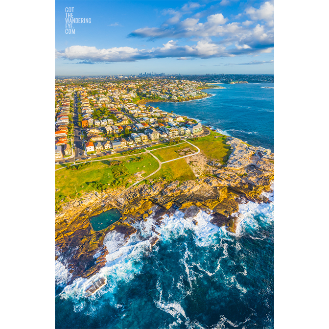 Aerial seascape above Mahon Pool, Mistral Point looking back to the Sydney city skyline by Allan Chan