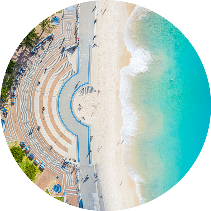 ChromaLuxe round metal print of the ocean. Aerial oceanscape above Coogee Beach promenade. Wall art delivered and ready to hang.