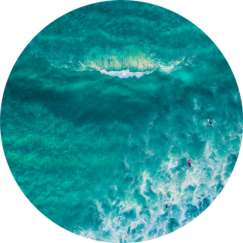 ChromaLuxe round metal print of the ocean. Aerial oceanscape above surfers approaching a glassy wave at Maroubra Beach. Wall art delivered and ready to hang.