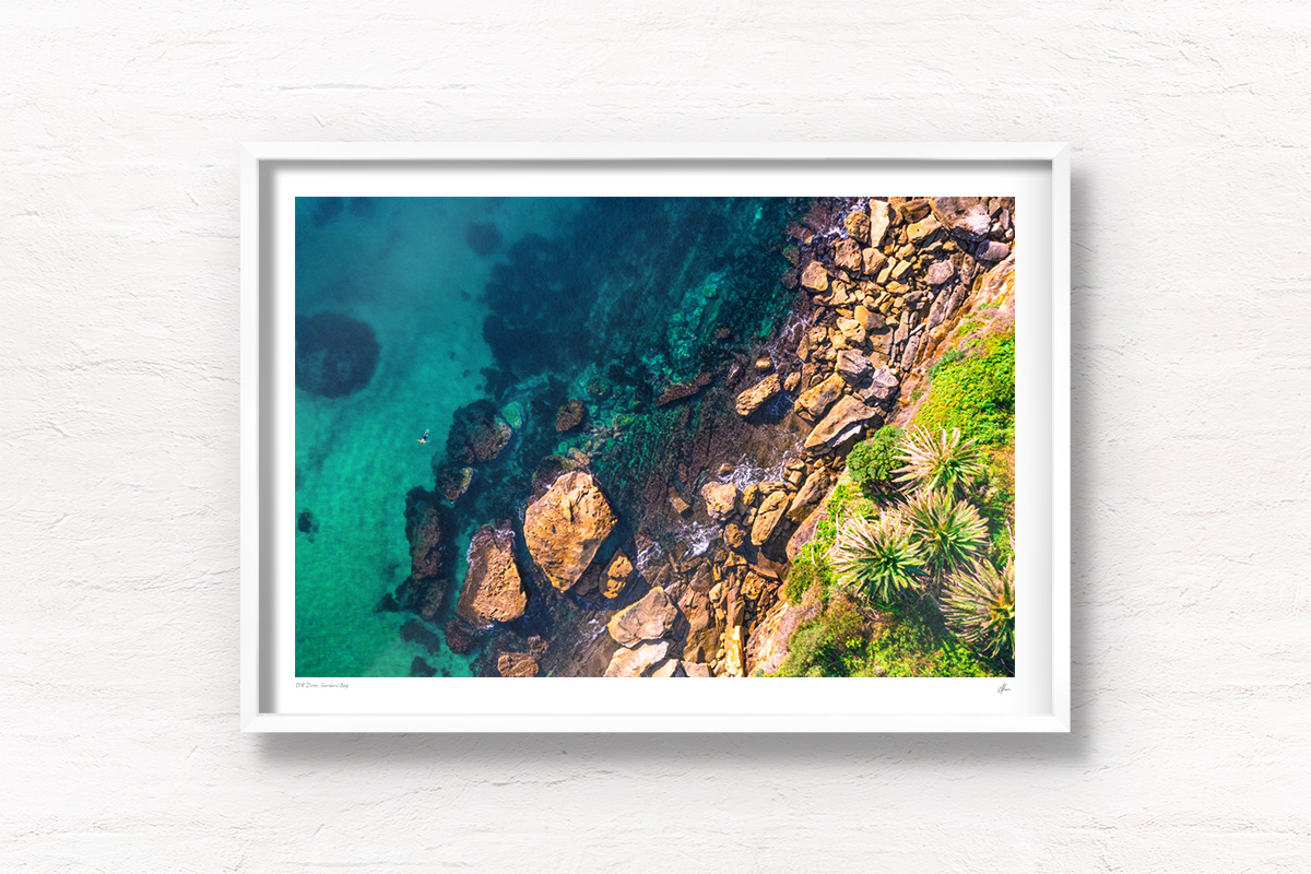 Framed wall art of man swimming in clear emerald waters of Gordons Bay, surrounded by palm trees and boulders from the clifftop.