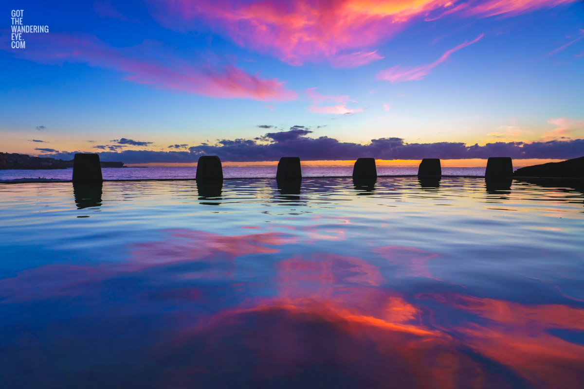 Incredible pink whispy cloud sunrise over glistening pink and blue waters Coogee at the Ross Jones Memorial Pool.