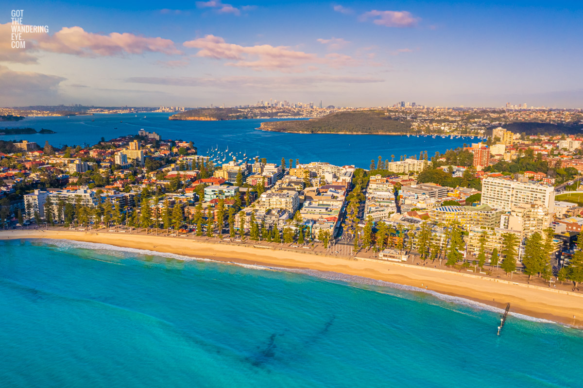 Manly beach bathed in a golden sunrise looking back towards North Harbour andt he Sydney city skyline.