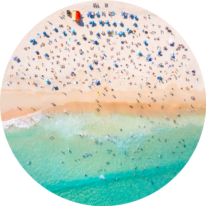 ChromaLuxe round metal print of the ocean. Aerial oceanscape above a packed Bndi Beach with blue beach umbrellas. Wall art delivered and ready to hang.