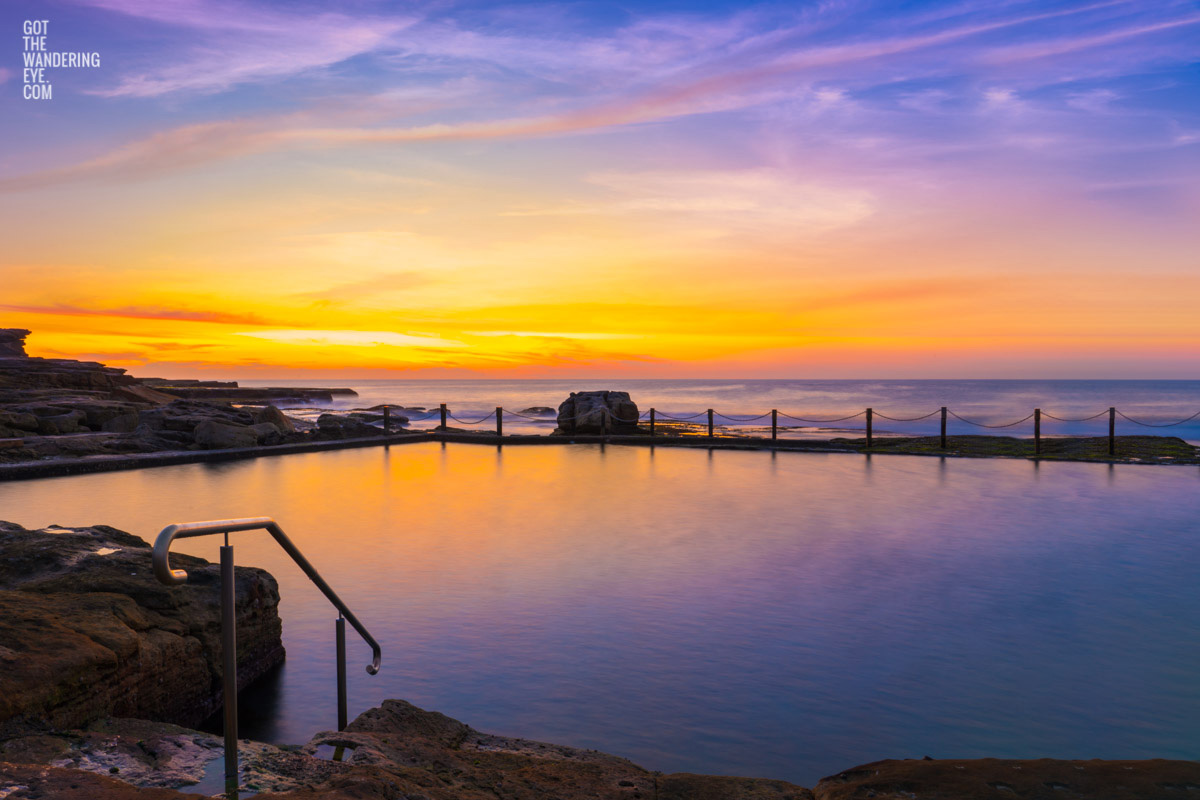 Passionfruit coloured sunrise over a empty long exposure of Mahon Pool at Maroubra