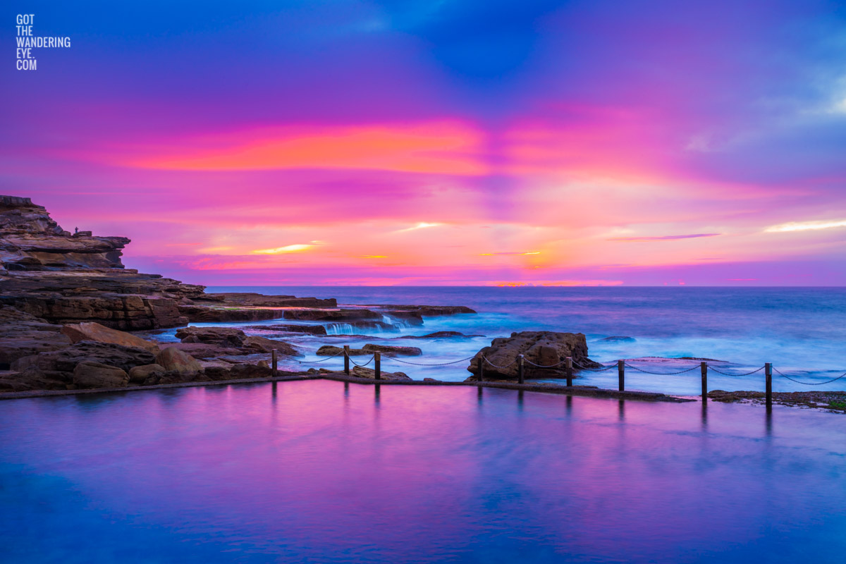 Pink and purple aurora sky, over a empty still Mahon Pool, Maroubra