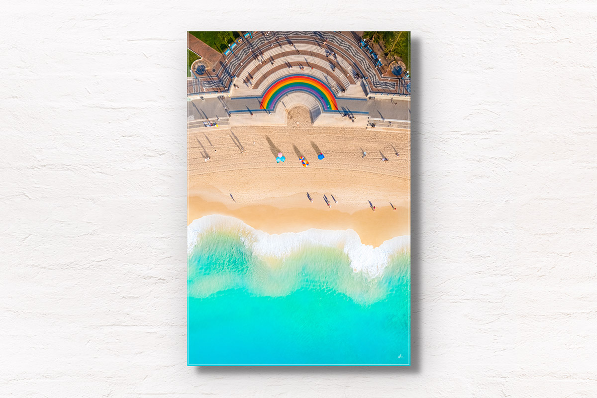 Vibrant 50 metre long rainbow on the promenade curving around the Coogee steps, as swimmers walk along the beach.