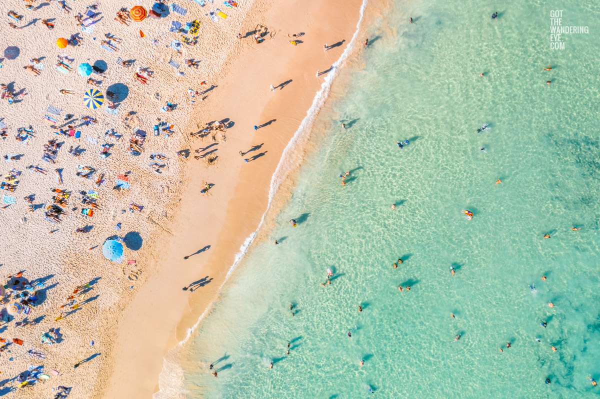 Swimmers and sunbathers enjoying a packed Bondi Beach with multi-coloured beach umbrellas on a Summers Day.