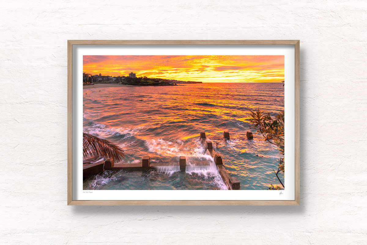 Swimmer enjoying a golden warm sunrise with waves crashing over the Ross Jones Memorial pool at Coogee